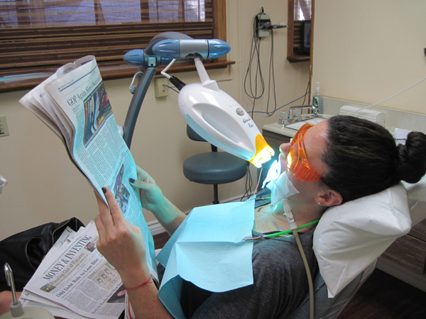 Patient reading a newspaper while undergoing Zoom Teeth Whitening
